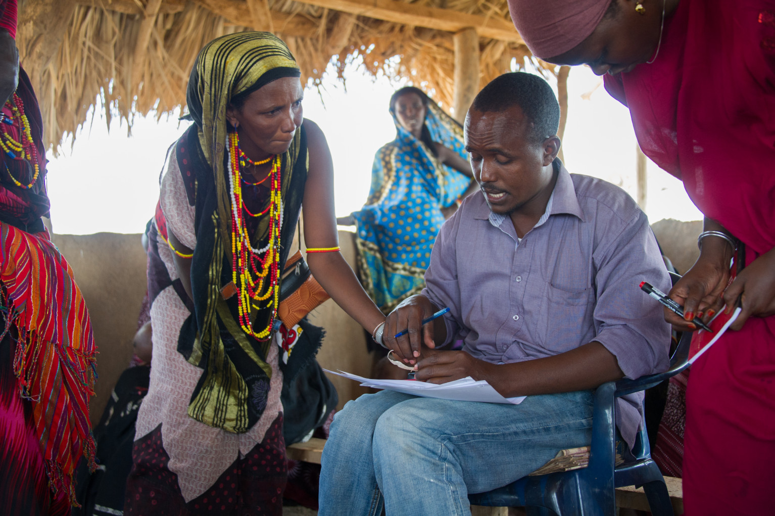 Dennis and Field Officer, Sabdio, help take down participants' information for their Savings Group. Each business group is given an additional grant during this training to help them increase their business stock.